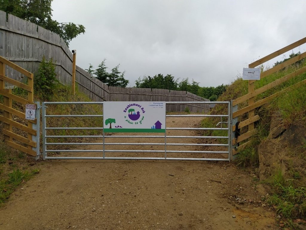 The picture shows the entrance gate to Enablement Ark. The gate is wide and mental and has an Enablement Ark purple and green sign on the front. Beyond the gate is the driveway that curves around to the right. The driveway has grassy banks and a tall wooden fence to the left.